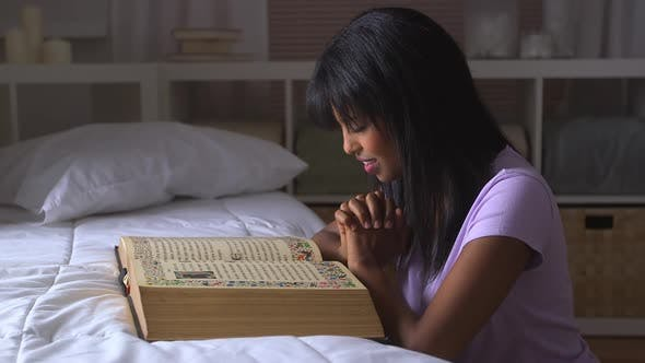 Thumbnail for African American girl praying with Bible on bed