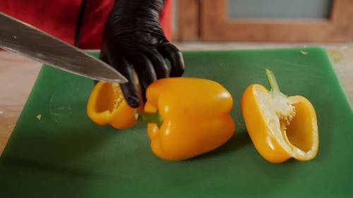 Close Up Cook Hands in Black Gloves Cut Yellow Bell Pepper with Knife