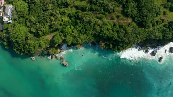 Overhead Aerial View of Tropical Waves Crashing Into Rocky Cliff on the Bali Coastline