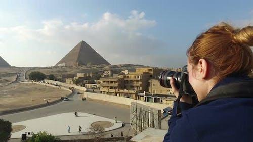 Woman taking photos of beautiful Giza pyramids complex