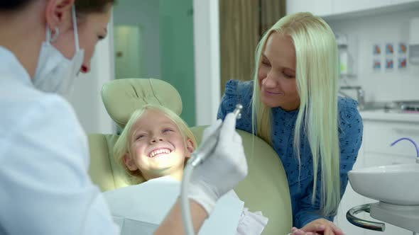Cover Image for Dentist Shows a Medical Drill, a Girl Laughs