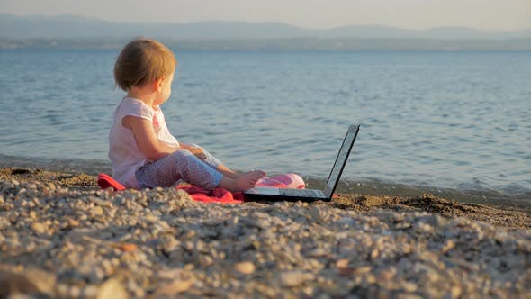 Thumbnail for Toddler Sitting with Notebook on Seashore. New Generation of People Who Combine Work and Vacation