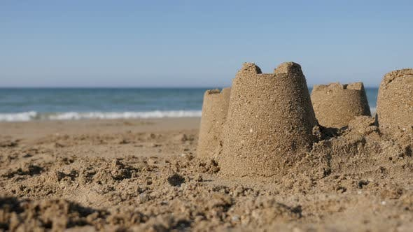 Thumbnail for Common summer vacation symbol with sand castles on ocean beach 4K 2160p UltraHD footage - Relaxing s