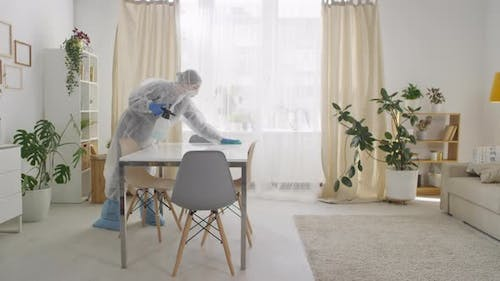 Woman in Full Body Protective Suit Disinfecting House