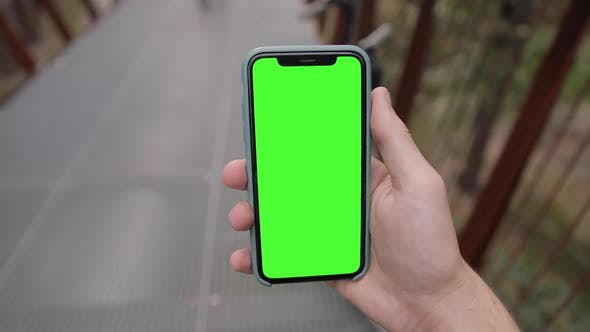 POV young man watching on iPhone 11 green mock-up blank screen walking outdoors in the park