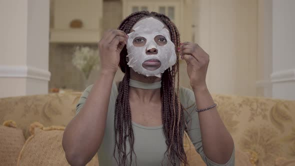 Cover Image for Portrait of Cute Beautiful African American Woman Putting Moisturizing Facial Mask on Her Face on