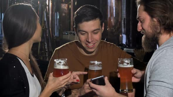 Thumbnail for Group of Friends Having Fun at Beer Pub, Using Smart Phone Together