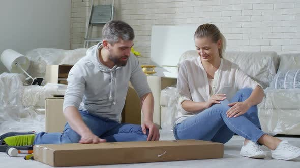 Thumbnail for Couple Opening Cardboard Box