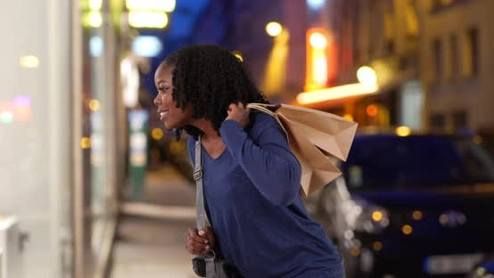 Thumbnail for Black woman walks over to look at elegant window display, shopping in evening