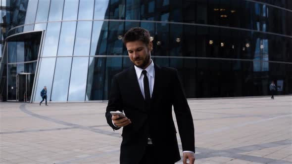 Thumbnail for Handsome Entrepreneur Reading Sms or Messenger Using App on Iphone in Business Centre