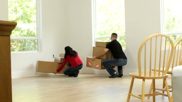 Thumbnail for Couple moving boxes into new home