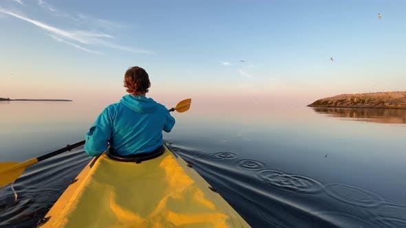 Man Sails Kayak Along Lake Water Against Island and Sky