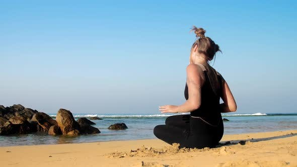 Thumbnail for Girl Changes Yoga Positions on Beach Against Blue Ocean