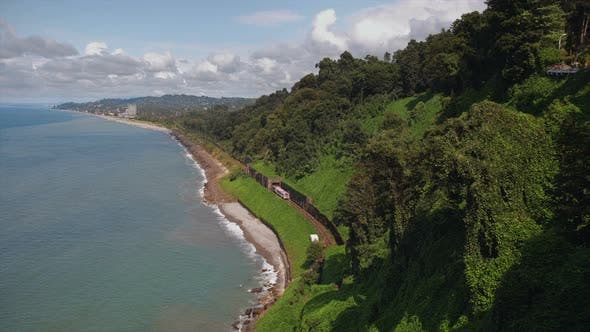 Thumbnail for Mountains Covered Trees, Cliff To Beach Sea with Railway Tracks Tunnel, Train Moving, Garden on Hill