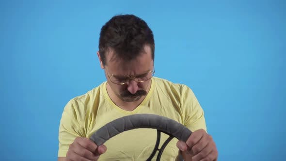 Funny Man Gets Into an Accident and Bangs His Head on the Steering Wheel on a Blue Background Slow