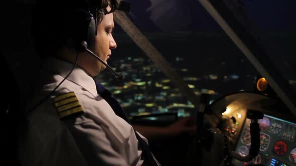Thumbnail for Professional Aircrew Commander Navigating Airplane Above City at Night Time