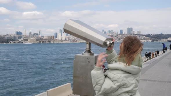 Traveler Woman Looking City Panorama By Tourist Binoculars to Bosporus Strait in Istanbul Turkey