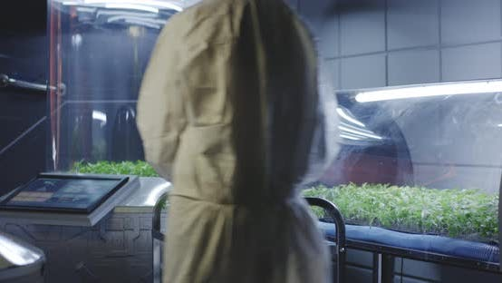 Thumbnail for Scientist in Hazmat Suit Checking Plant Incubators