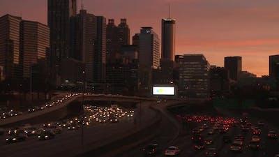 Panning, medium wide, nighttime shot of the Atlanta Skyline with traffic below.