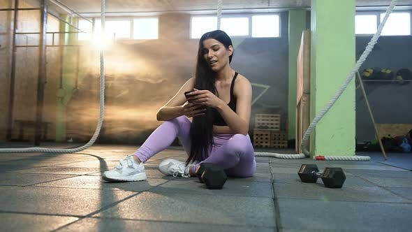 Thumbnail for Attractive Fit Woman Using Smart Phone while Resting After Training in the Gym