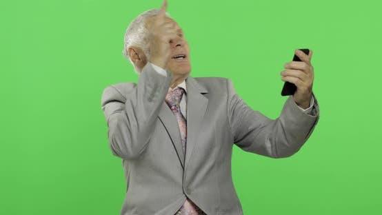 Thumbnail for Handsome Elderly Businessman Having Video Chat Using Smartphone. Chroma Key
