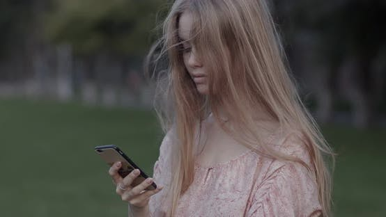 Thumbnail for Beautiful young girl is looking at the phone