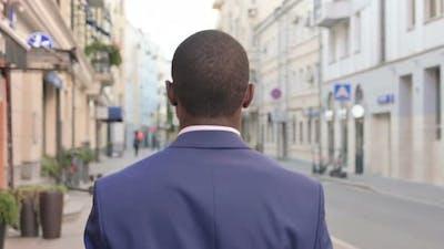 African Businessman Walking on Street Back View