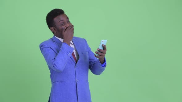 Cover Image for Happy Young African Businessman Using Phone and Looking Surprised