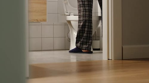 Adult man walks to a toilet at home in the night
