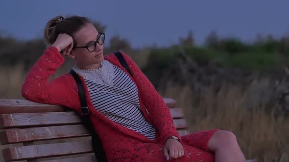 Thumbnail for Girl in Glasses Sitting on Bench Watching the Evening Sea