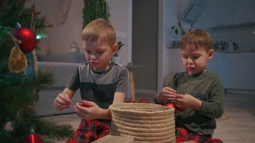 Two Boys 35 Years Old Together Decorate the Christmas Tree Before Christmas