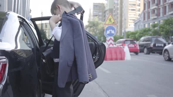 Cover Image for Serious Well-dressed Boy Getting Out of the Car and Walking Down the Street