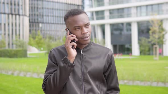 Thumbnail for A Young Black Man Talks on a Smartphone with a Smile - Office Buildings in the Blurry Background