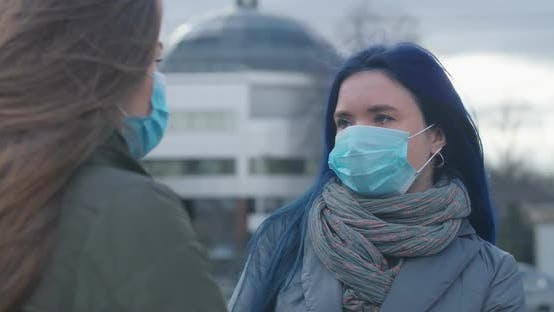 Cover Image for Close-up Portrait of Young Woman in Protective Mask Standing on City Street and Talking with