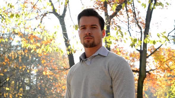 Thumbnail for Handsome Young Satisfied Guy Stands in the Forest and Looks To Camera- Sun Rays