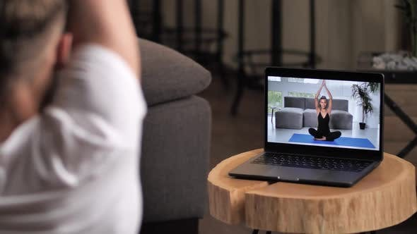 Man Practicing Yoga Online with Woman Instructor