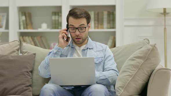 Cover Image for Young Man with Laptop Talking on Smartphone at Home