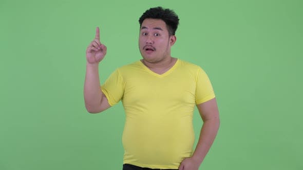 Thumbnail for Happy Young Overweight Asian Man Pointing Up