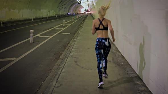 Attraktive Frau Joggen durch einen Tunnel