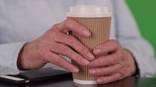 Close up of elderly person's hands grabbing coffee cup on green chroma key