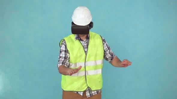 Man in a Helmet and Uniform Uses a VR Helmet