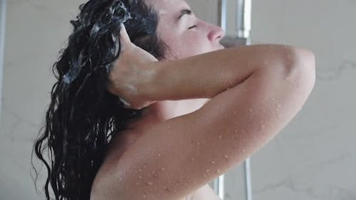 Pretty Young Woman Washes Away the Shampoo From Her Hair While Standing Under a Warm Shower Stream
