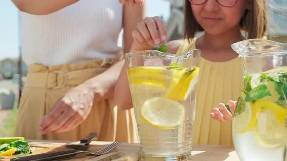 Mädchen fügt Minze zu hausgemachter Limonade hinzu