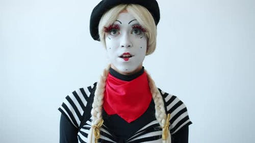 Portrait of Beautiful Female Mime Rolling Eyes and Smiling on White Background
