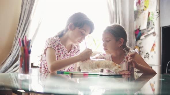 Thumbnail for Kinder zeichnen zusammen auf einem verputzten Arm in einer Bandage. Schwester ermutigt und kümmert sich um einen Kranken