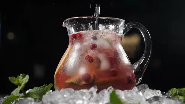 Pouring Pure Sparkling Cold Water Into Transparent Glass Jar with Lime Ice Cubes and Berries