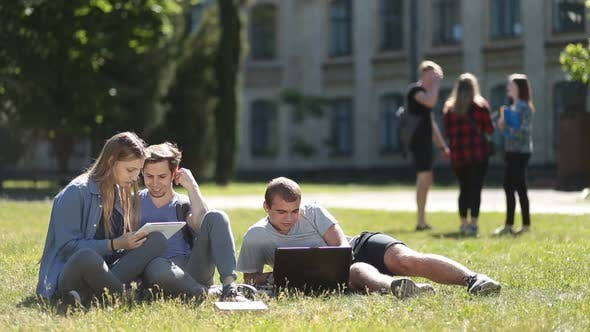 Thumbnail for College Students Using Laptop and Tablet on Lawn