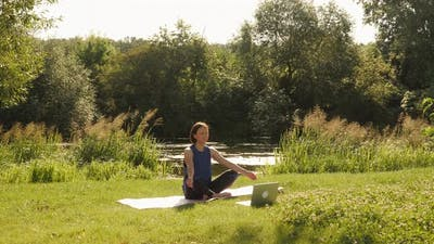 Practicing yoga and meditating in park with laptop.
