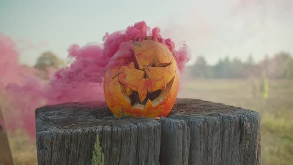 Spooky Carved Halloween Pumpkin with Red Smoke