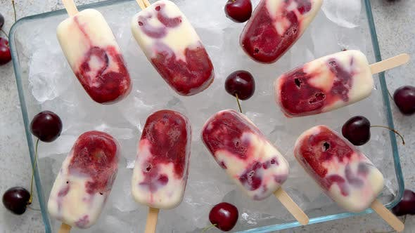 Homemade, Delicious, Cherry and Milk Ice Cream Popsicles Placed on Glass Tray Filled with Ice Cubes